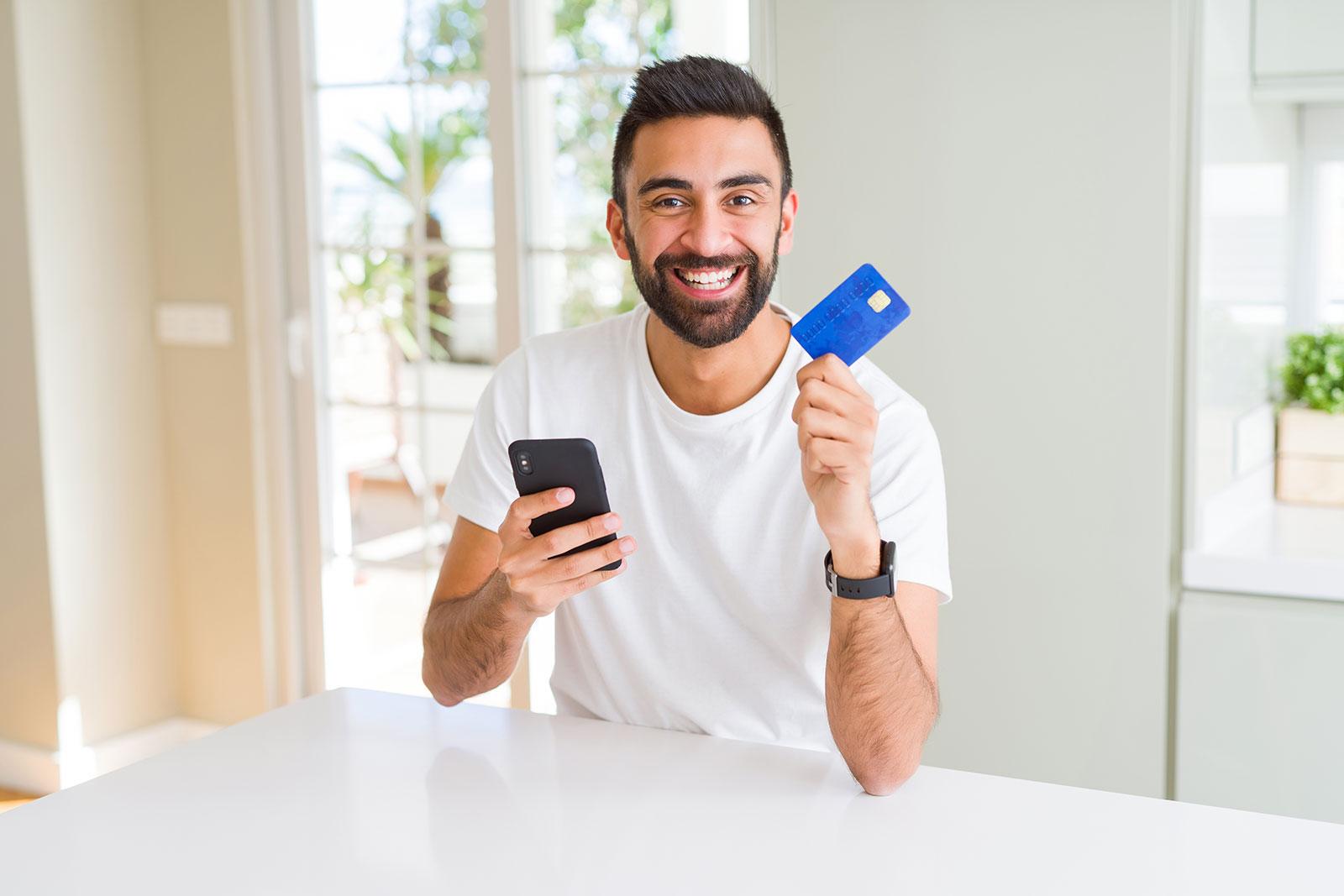 Testperson im Einzelinterview mit Handy und Kreditkarte in der Hand